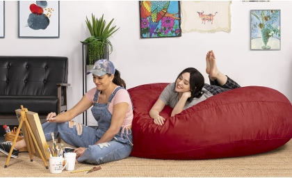 Model relaxing and painting while sitting on the Jaxx Cocoon Bean Bag in Cinnabar color