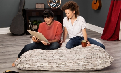 Two girls looking at records on the Pillow Saxx 5' Bean Bag