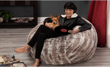 Woman with dog looking at records while sitting on the Saxx 4' Bean Bag Chair - Faux Fur