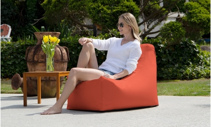 Woman sitting on the flamingo color Juniper Outdoor Bean Bag Chair