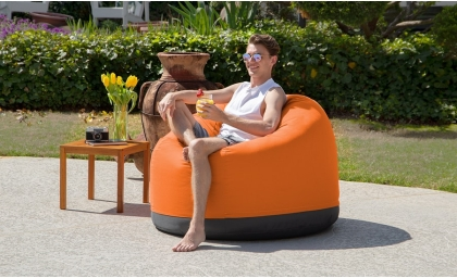 Man relaxing on the Palmetto Outdoor Bean Bag Club Chair - Sunbrella