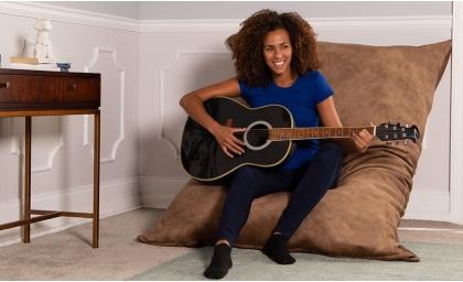 Woman playing guitar on the Microvelvet Pillow Saxx Giant Bean Bag