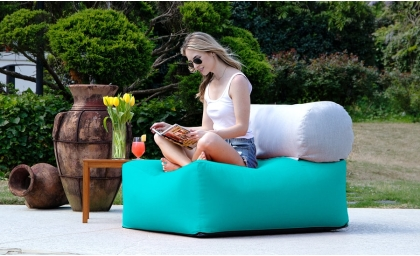 Woman reading on the Tybee Outdoor Lounger - Sunbrella