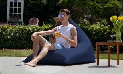 Man drinking juice on the Twist Outdoor Bean Bag Chair